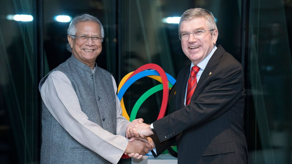 Image shows Muhammad Yunus greeting International Olympic Committee President Thomas Bach during a ceremony held in 2020