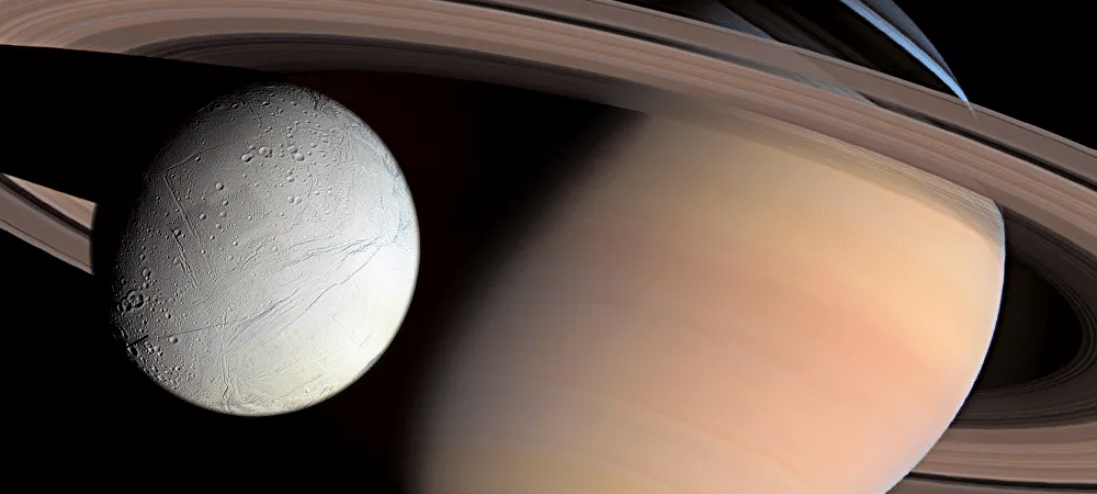 Ilustração mostra a lua Encélado sobrevoando Saturno, que está ao fundo