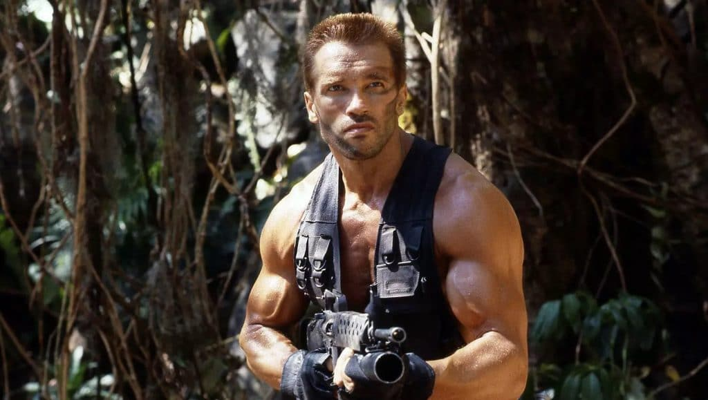 Photo shows Arnold Schwarzenegger in a scene from the first film, in a jungle.