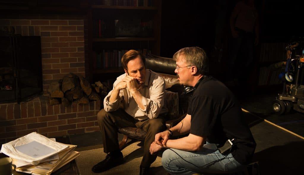 Bob Odenkirk conversa com Vince Gilligan em set de 'Better Call Saul'. Os dois podem ser vistos em uma sala escura, e o ator parece receber instruções do diretor.