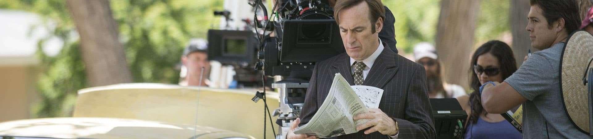 Ator Bob Odenkirk aparece trajando terno e segurando jornal em foto que registra filmagens de Better Call Saul