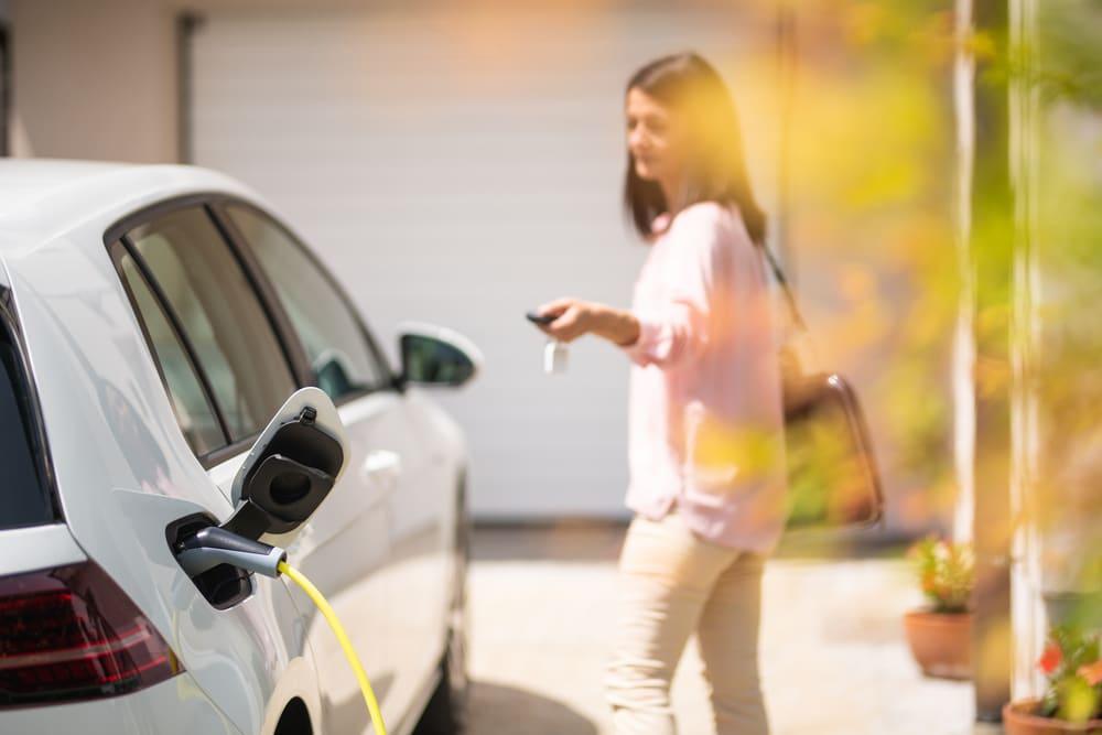 Mulher em pé ao lado de um carro elétrico sendo carregado