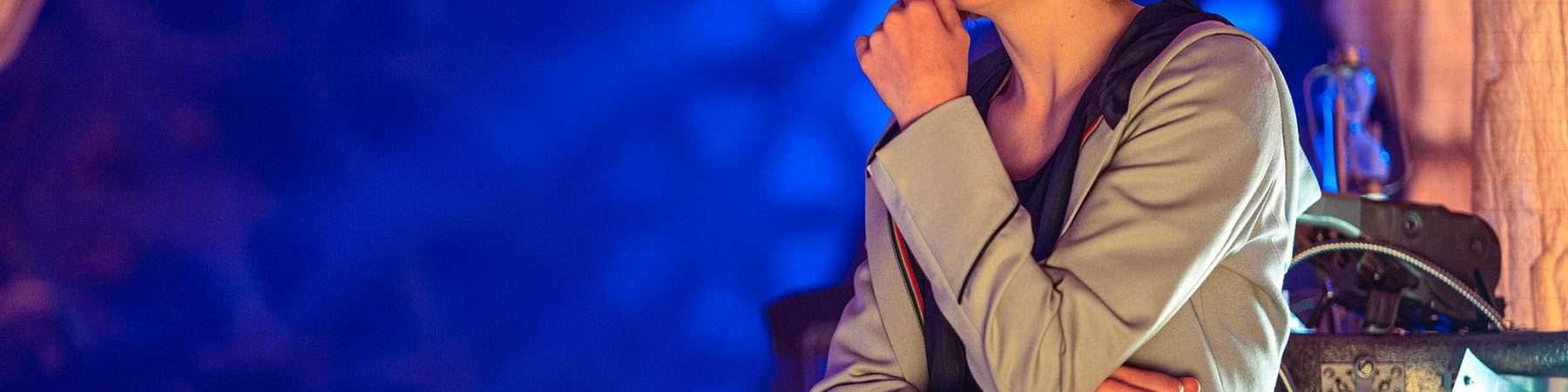A atriz Jodie Whittaker caracterizada como Doctor aparece em foto com a mão no queijo e olhar pensativo.