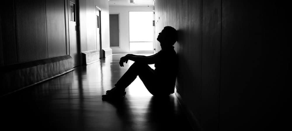 Homem sentado em um corredor escuro