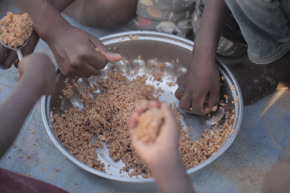 Crianças colocando as mãos em um prato de comida
