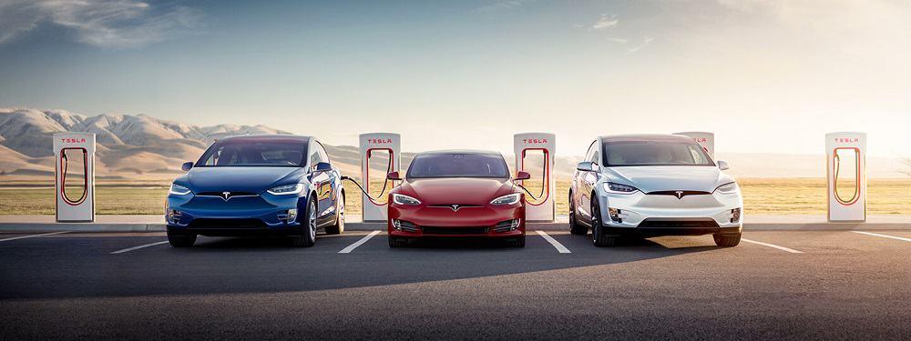 Três carros da Tesla sendo carregados