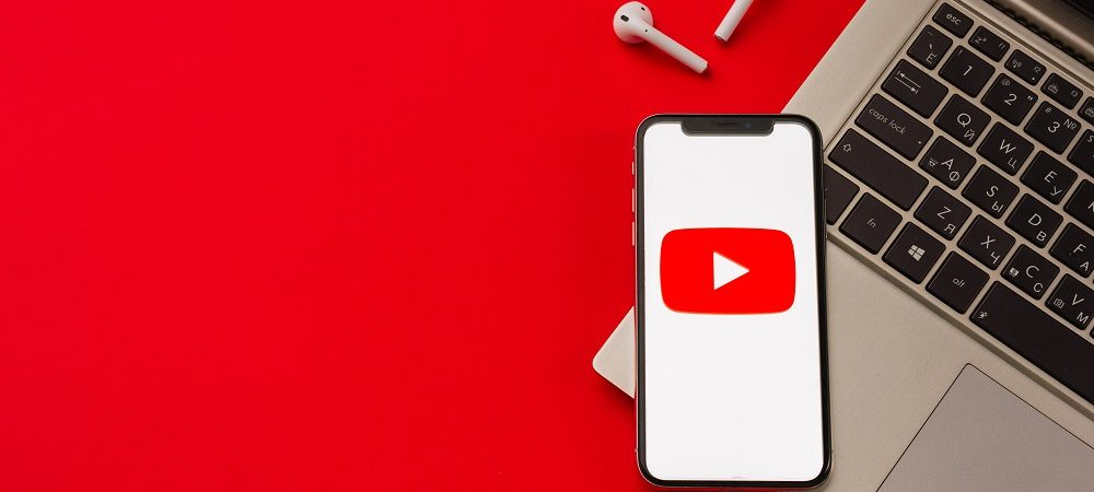 Imagem mostra logo do youtube na tela de um smartphone que, por dua vez, encontra-se em cima de um teclado de notebook. O fundo da imagem é vermelho