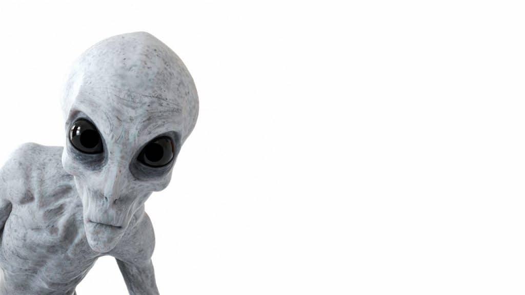 Ilustração em 3D mostra um alienígena com corpo de cor cinza, olhos pretos e avantajados olhando para o espectador à frente de um fundo branco