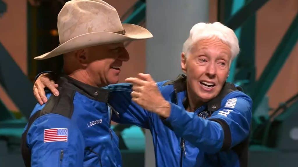 Imagem mostra Jeff Bezos, vestindo roupa de astronauta e um chapéu de caubói, abraçando Wally Funk, a pessoa mais velha a ir para o espaço, durante coletiva de imprensa da Blue Origin