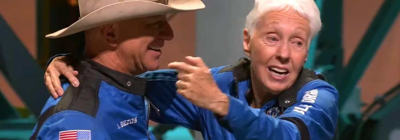 La imagen muestra a Jeff Bezos, vestido con traje espacial y sombrero de vaquero, abrazando a Wally Funk, la persona de mayor edad en ir al espacio, durante una conferencia de prensa de Blue Origin.