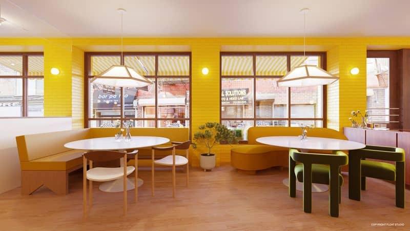 Imagem mostra, ao fundo, janelas abertas em uma parede amarela; à frente mesas com cadeiras dispostas no espaço que é a parte interna do Bumble Brew, restaurante físico do aplicativo de econtros Bumble