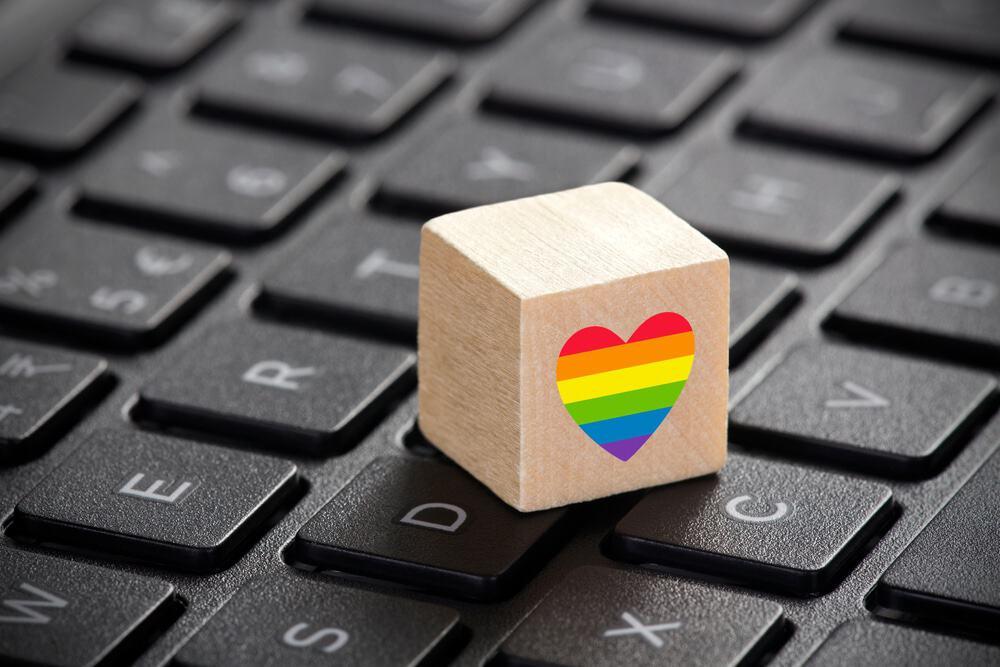 Imagem mostra um cubo de madeira com um coração nas cores do arco-íris colocado em cima de um teclado de notebook