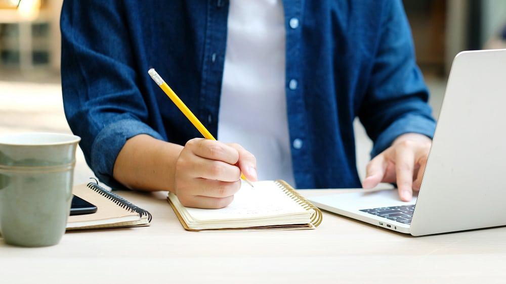 homem estudando escrevendo em caderno e notebook