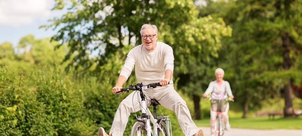casal idosos andando de bicicleta em parque