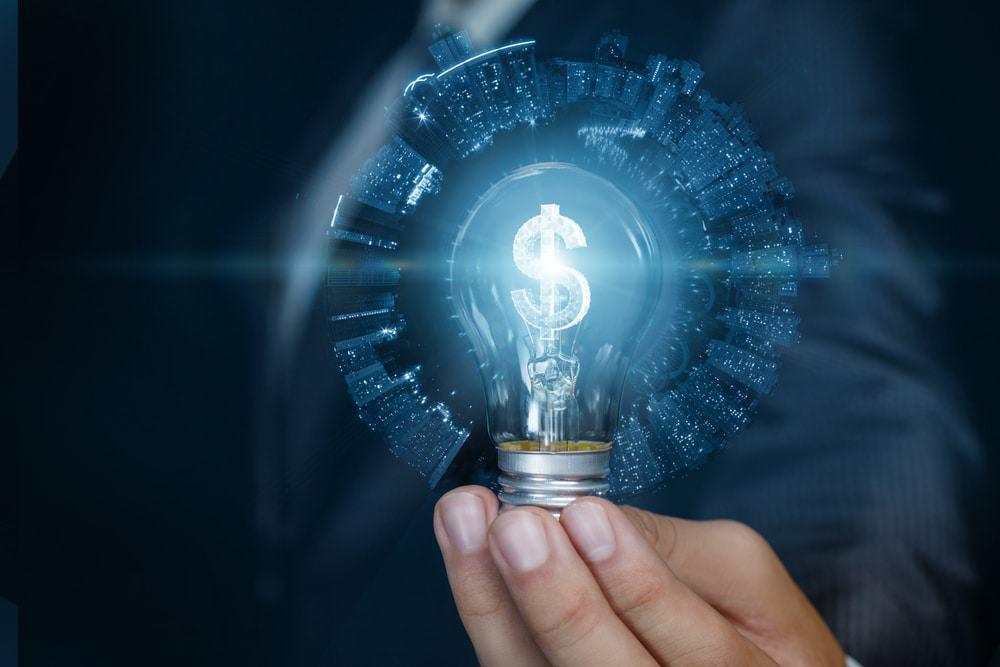 Empresário mostrando a lâmpada com holograma de dinheiro em chamas dentro, com fundo azul