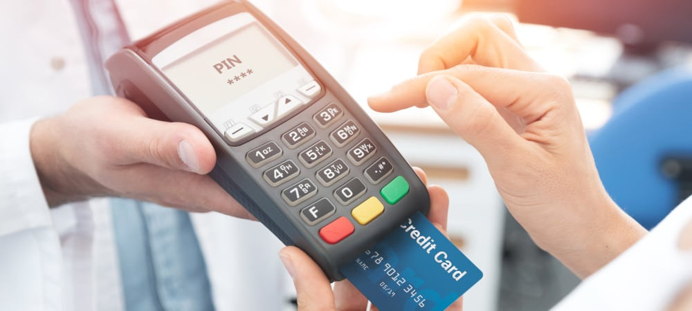 """Consumer paying for a purchase with a credit card on a portable """"little machine"""""""