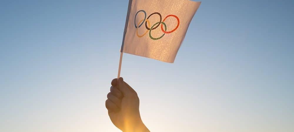 Mão segurando bandeira com símbolo das Olimpíadas