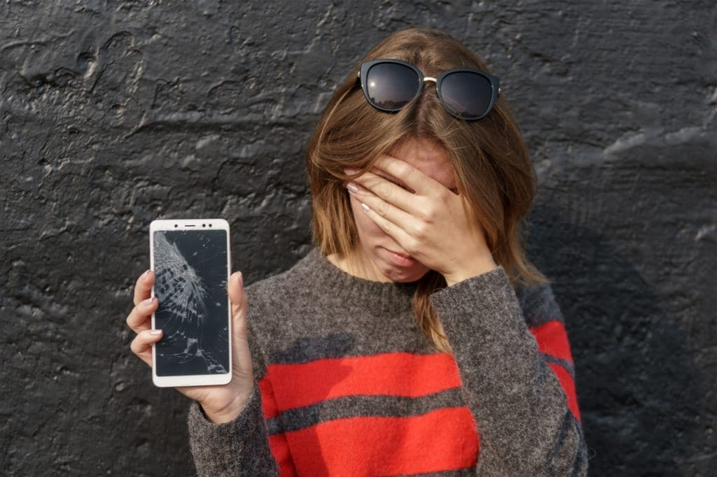 Image shows a woman holding a smartphone with a broken screen. President Joe Biden wants to change the repair rule, which recommends only the use of technical assistance provided to manufacturers