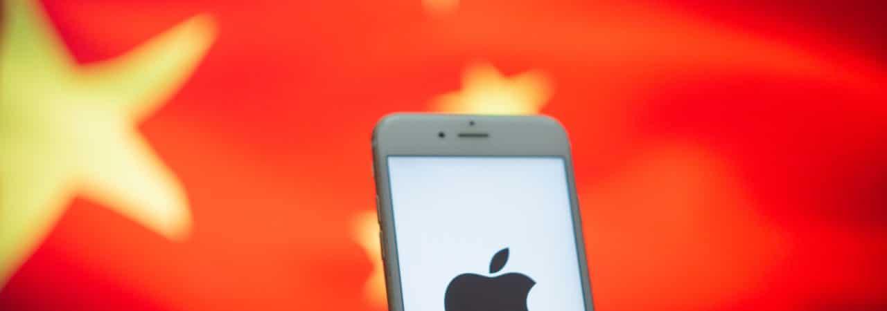 Um smartphone é exibido à frente da bandeira chinesa, com o logotipo da Apple em sua tela