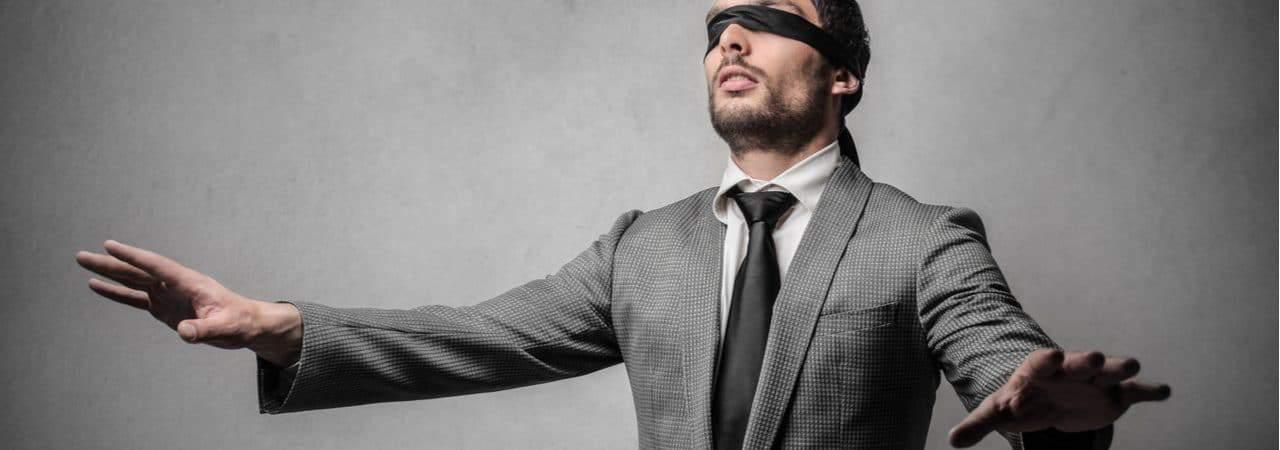 Imagem mostra um homem de terno e gravata, com os olhos vendados e mãos esticadas, como se estivesse tentando navegar sem os olhos