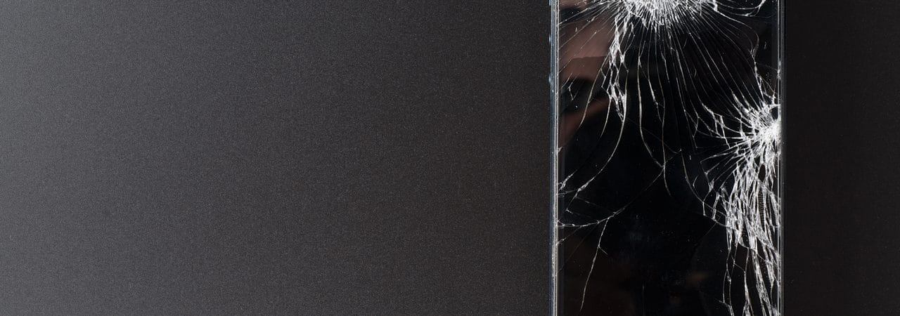 Photo shows an iPhone with a broken screen, in front of a black background