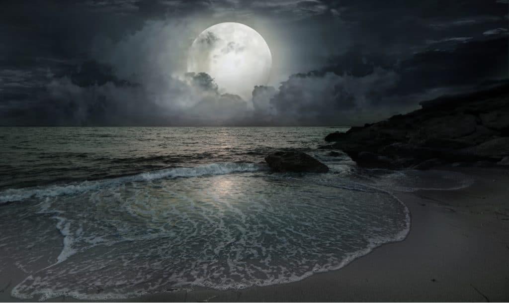 La imagen muestra la luna envuelta en nubes desde un cielo nocturno, con las aguas del mar moviéndose debajo de ella. Un estudio de la NASA indica que es probable que la órbita de la Luna cause más inundaciones para 2030.