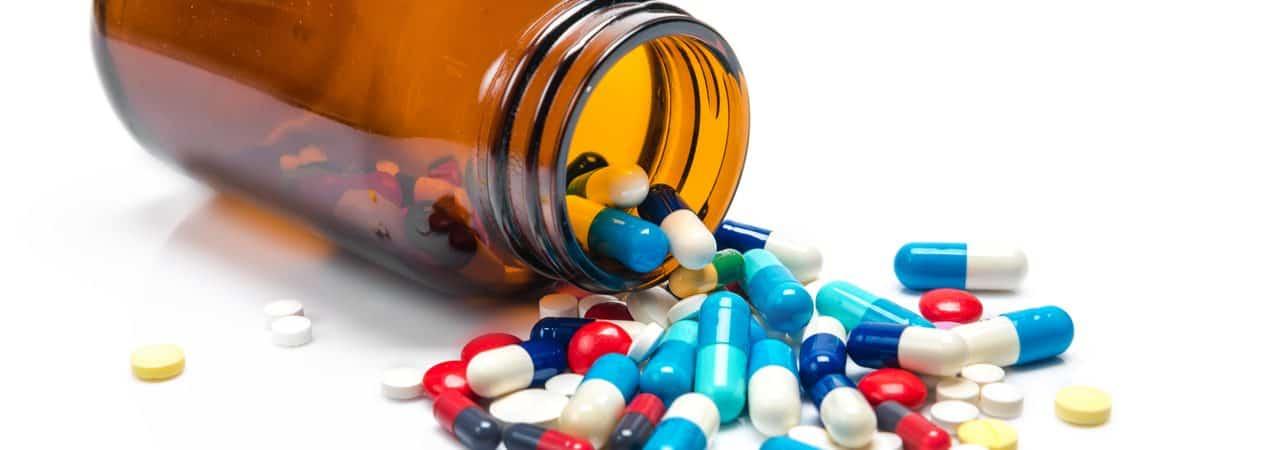 Imagem mostra várias pílulas medicinais despejadas de um frasco de vidro
