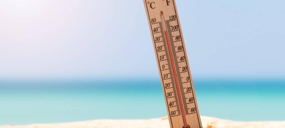 termometro fincado na areia da praia mostrando calor