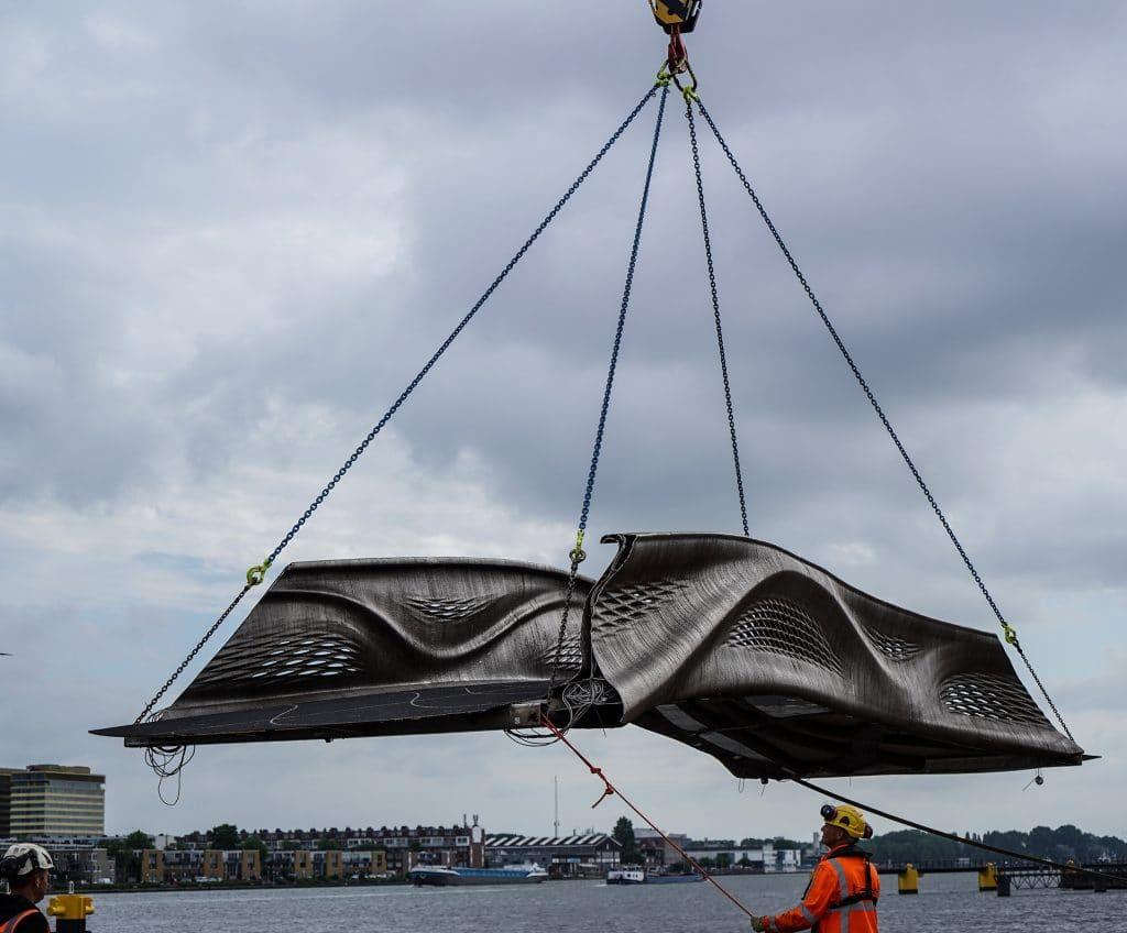 Foto mostra a ponte feita em impressão 3D na Holanda, sendo instalada por uma grua robótica com uma série de cabos conectados