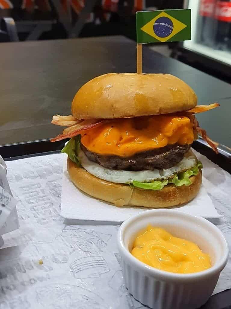 Foto mostra um hambúrguer artesanal, com molho à frente, em cima de uma bandeja