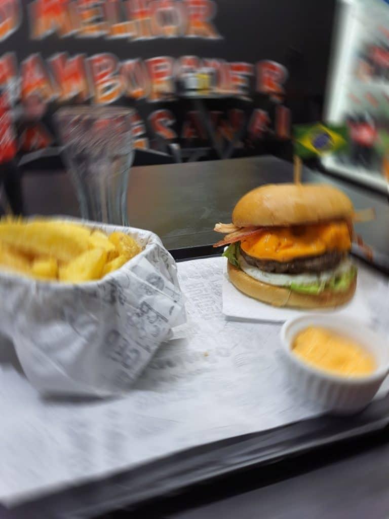 Foto mostra um hambúrguer artesanal, acompanhado de batatas e molho. A imagem tem um filtro de desfoque, gerado pela inteligência artificial do smartphone Galaxy M62