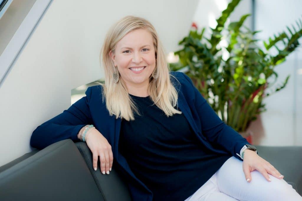 Ashley Gjøvik sentada sorrindo em um sofá cinza com um vaso de platas verdes ao fundo. Ela foi afastada da Apple após denunciar discriminação de gênero.