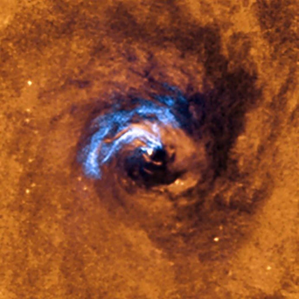A imagem mostra o processo de alimentação nuclear de um buraco negro na galáxia NGC 1566, e como os filamentos de poeira, que circundam o núcleo ativo, são aprisionados e giram em espiral ao redor do buraco negro até engoli-los