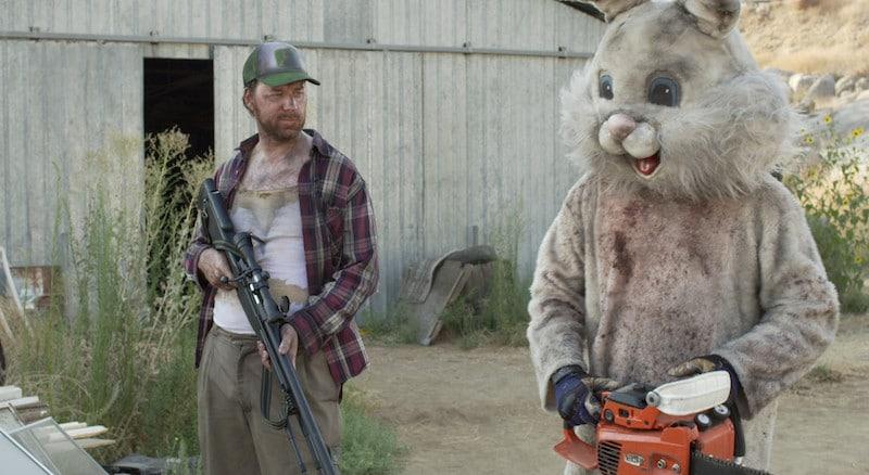 Imagem mostra homem armado ao lado de uma pessoa fantasiada de Coelho da Páscoa.