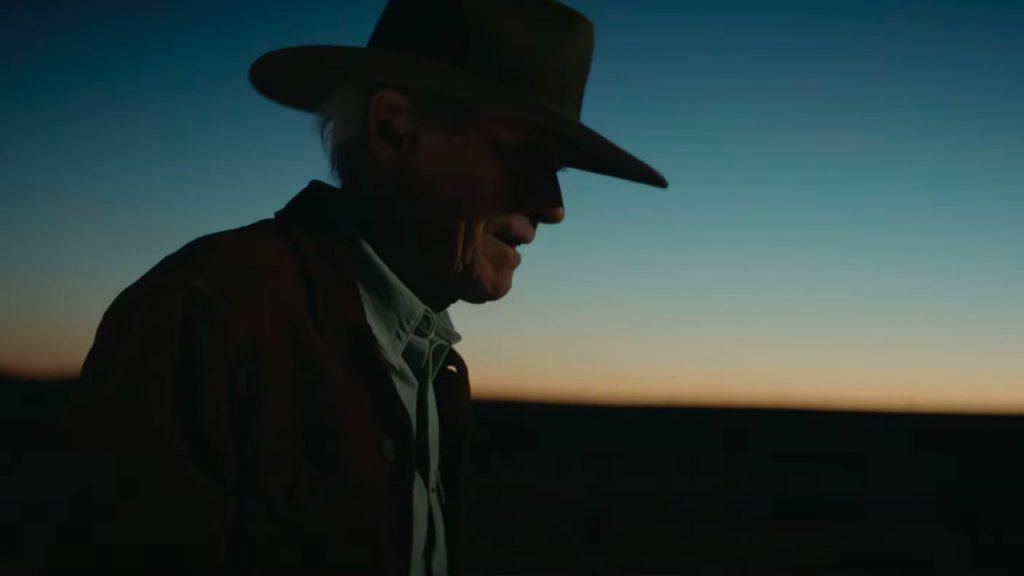 Foto mostra Clint Eastwood de perfil, usando jaqueta e chapéu, com o horizonte ao fundo em que, aparentemente, o sol se põe