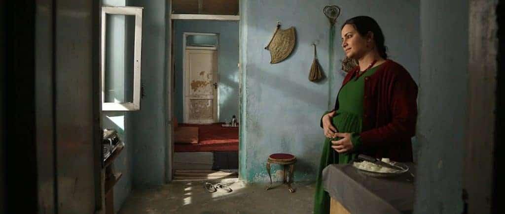 Cena do filme 'Hava, Maryam, Ayesha', de Sahraa Karimi. A personagem grávida está do lado direito da imagem, tocando a barriga.
