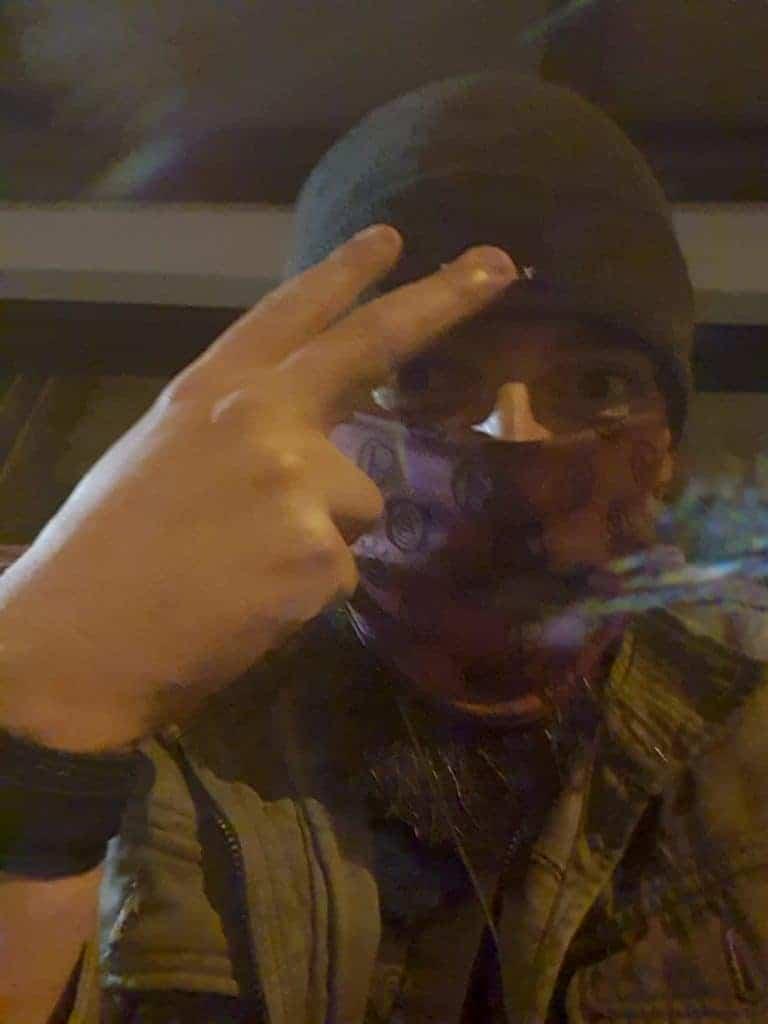 Foto mostra um homem vestindo touca e máscara de tecido, com dois dedos apontados para cima, em ambientação noturna. A imagem é um teste da câmera frontal do Samsung Galaxy M62