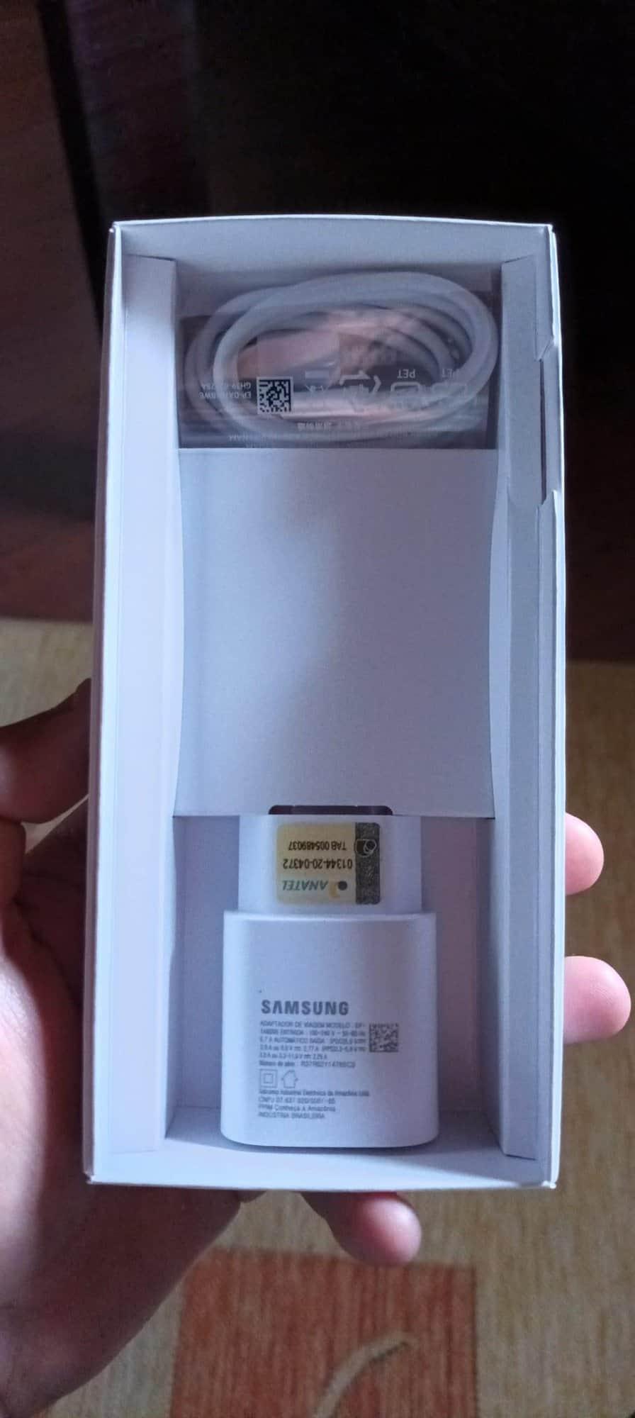 Imagem mostra o conteúdo que vem na caixa do smartphone Galaxy M62 - especificamente, um adaptador de tomada e o cabo USB, mas nenhum fone. Samsung lançou o Galaxy M32 e o Galaxy M62 no varejo online brasileiro em 2 de agosto