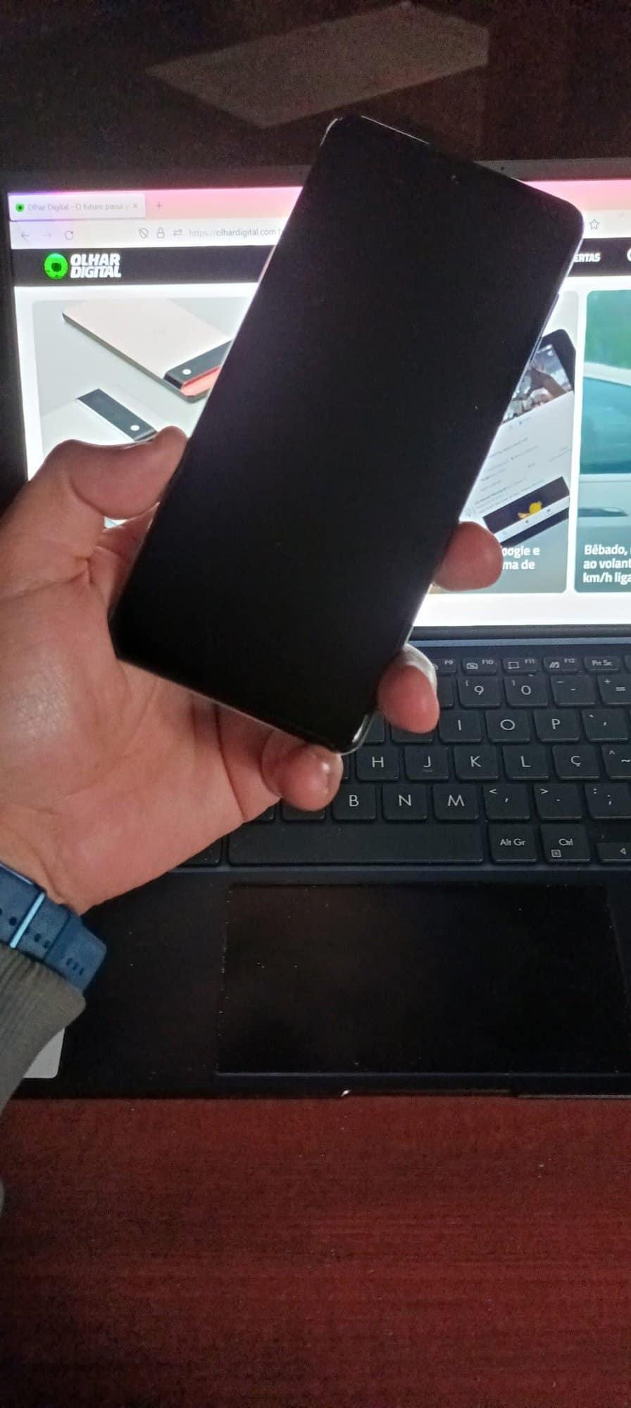 Imagem mostra a tela da frente do Galaxy M62, sendo segurado por uma mão e um notebook exibindo a página inicial do Olhar Digital ao fundo. Samsung lançou o Galaxy M32 e o Galaxy M62 no varejo online brasileiro em 2 de agosto