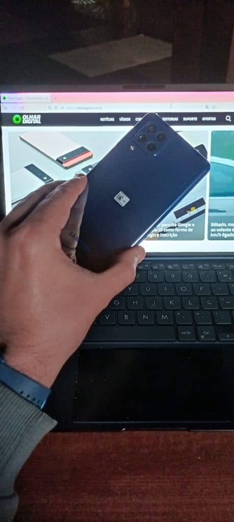 Imagem mostra a parte traseira do Galaxy M62, sendo segurado por uma mão e um notebook exibindo a página inicial do Olhar Digital ao fundo. Samsung lançou o Galaxy M32 e o Galaxy M62 no varejo online brasileiro em 2 de agosto