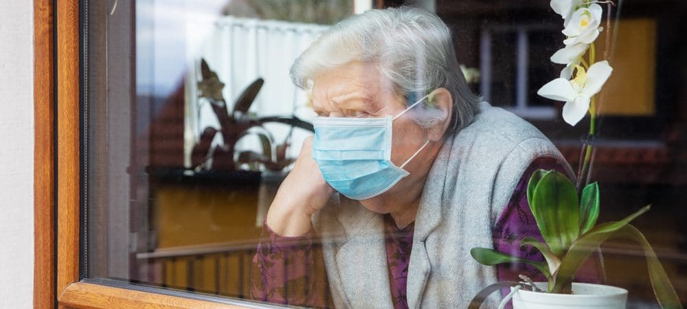 Elderly woman in mask looking out the window