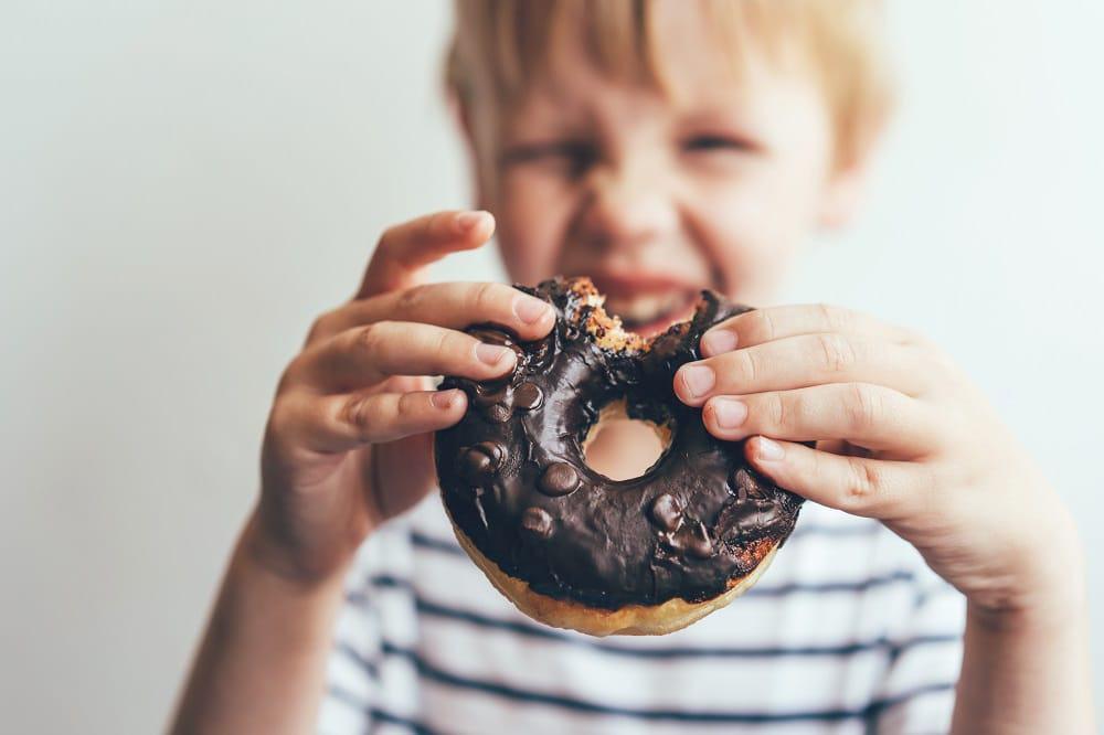 Criança comendo rosquinha de chocolate