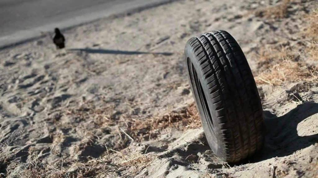 Foto mostra pneu em primeiro plano e, ao fundo, o que aparenta ser uma pessoa sentada.