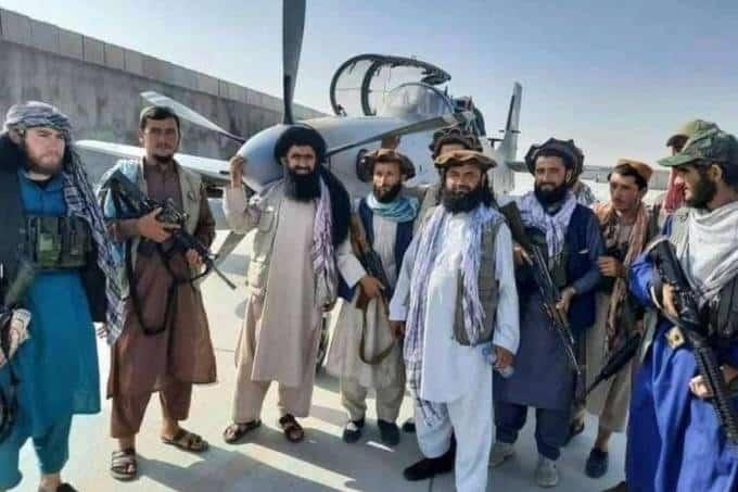 Radicais do Talibã em frente a um Super Tucano