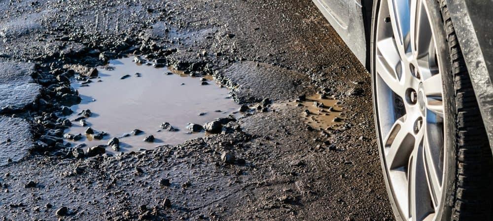 Roda de carro perto de um buraco na estrada