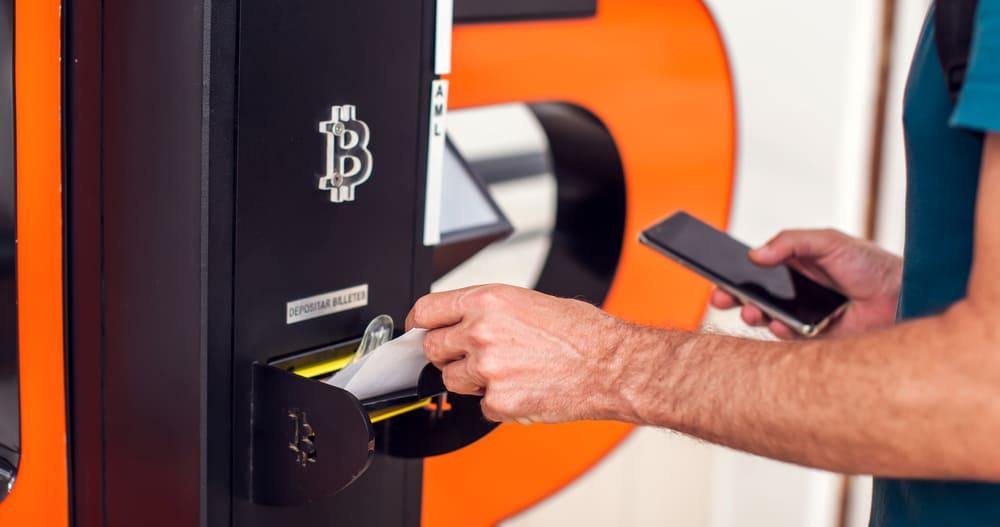 Imagem mostra uma mão masculina realizando uma transação em bitcoin por meio de um caixa eletrônico