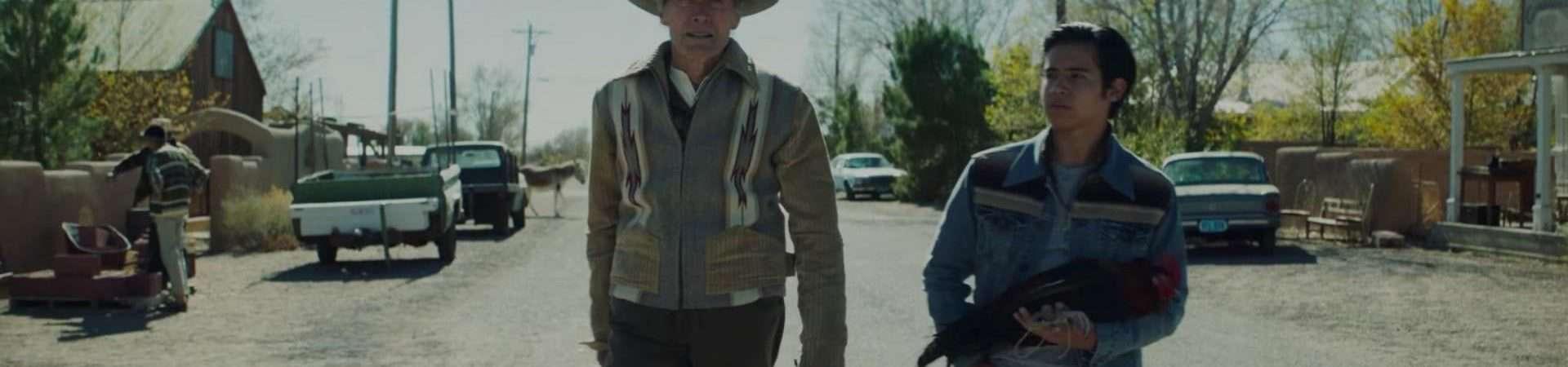 Foto mostra Eastwood e Eduardo Minett caminhando no meio de uma rua em área urbana. O garoto carrega nos braços um galo.