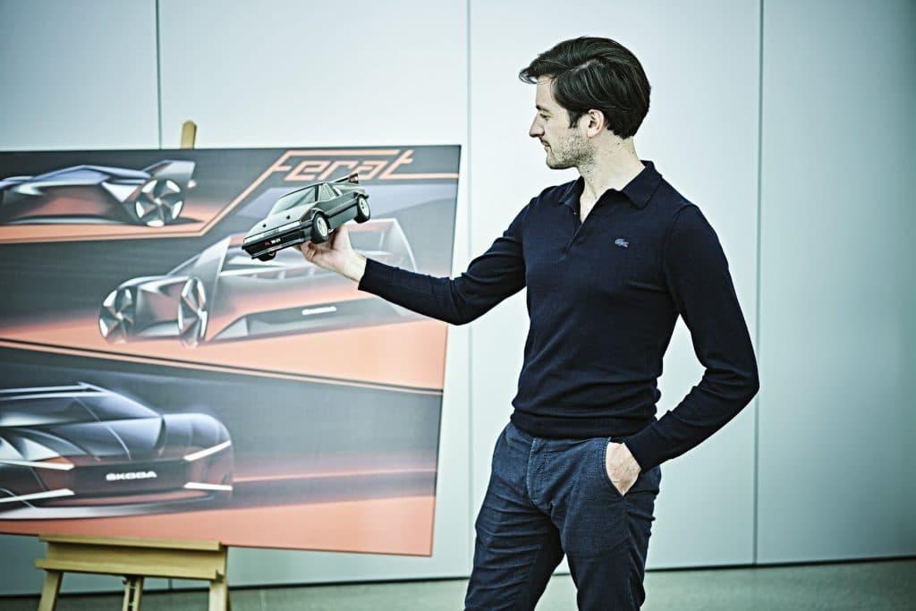 O designer Baptiste Brugiere segurando um mini modelo do Skoda Ferat ao lado de uma tela com desenhos do seu conceito do carro