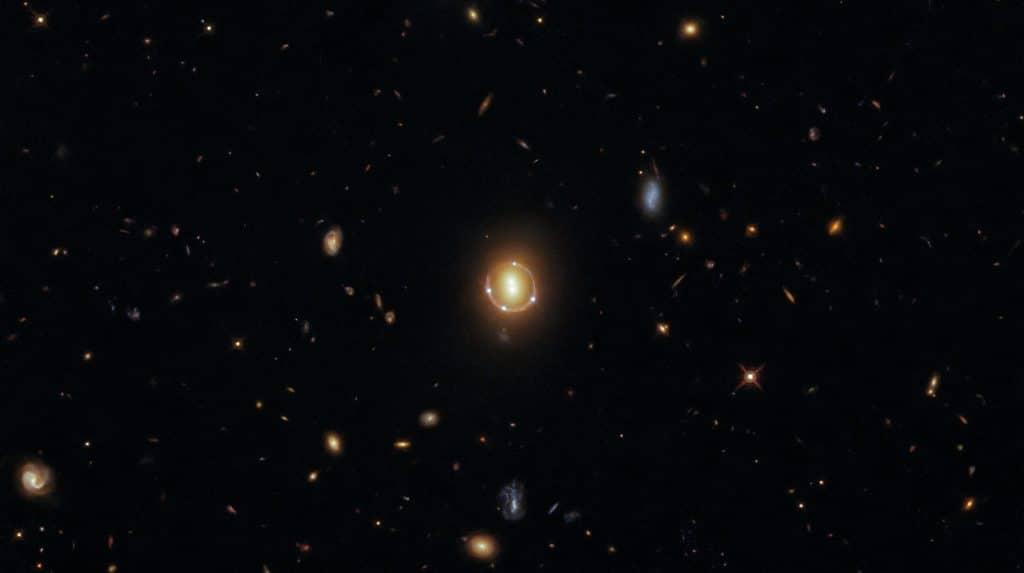 Imagem mostra o efeito de lente gravitacional previsto por Albert Einstein, fotografado pelo Hubble. A foto mostra quatro pontos de luz circulando outros dois pontos centralizados, mas na verdade são apenas três corpos