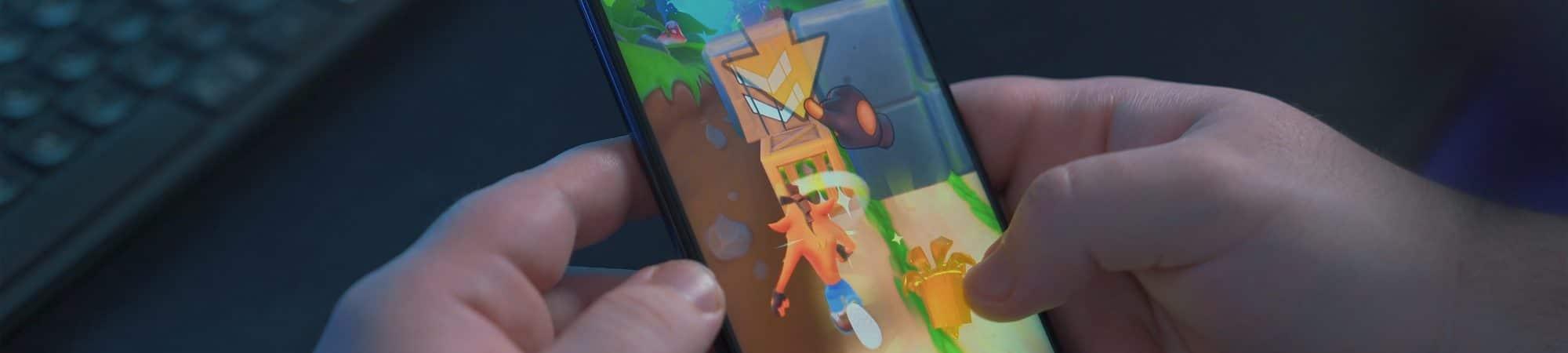 App Google Play Games terá novos recursos no Android 12. Imagem mostra mãos jogando em smartphone disposto na vertical. Imagem: Onur Binay/Unsplash